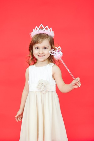 girl magic wand: Vertical portrait of beautiful girl dressed in fairy isolated on red background. Cute little kid wearing a crown and white dress holding a magic wand.