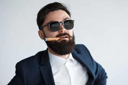 Lamber like male model with moustache and beard wearing black suit and smoking cigar isolated on white background