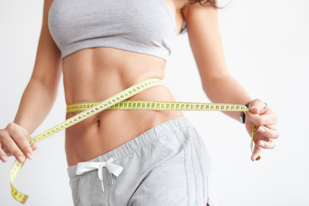 waistline: Woman measuring her waistline. Closeup of female with perfect slim body and torso. Healthy nutrition and weight losing concept.