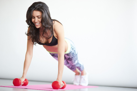 pushup: Young brunette woman doing push-up on mat with dumbbells. Female training with pushup exercise on white background Stock Photo