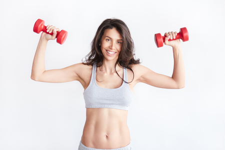Smiling athletic woman pumping up muscles with red dumbbells isolated on white background. Strong fit brunette female fitness trainer