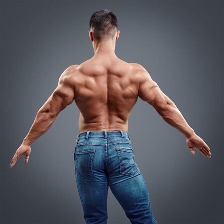 Male bodybuilder flexing his back muscles on grey background. Back view of one muscular athletic man showing flexing