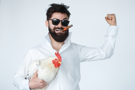 cockfighting: Bearded Man holding Thai Fight cock. Illegal gambling concept. Winner