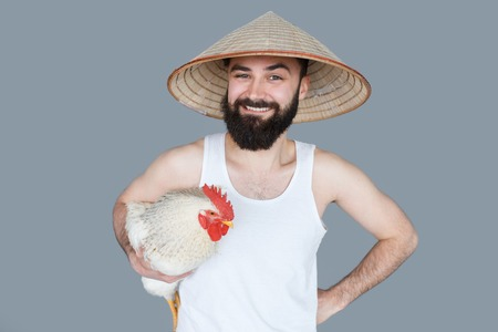 explorer man: Young explorer man with beard and vietnamese hat holding a cock isolated on grey backgroun. Crazy travel concept