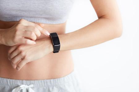 Закройте дисплей фитнес-зоны. Женщина, проверка ее здоровье отслеживания носимое устройство на белом фоне. Черный пустой экран Фото со стока