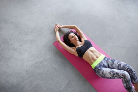 Top view of woman lying on floor with her eyes closed and stretched arms. Fitness woman exercising on yoga mat and concrete grunge grey floor