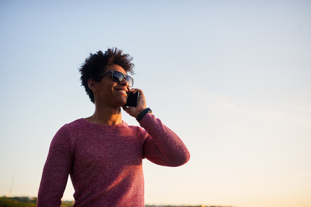 uplifting: Young happy smiling urban man using smart phone. Handsome curly young black african man talking on mobile smartphone on sunset sky background. Inspring and uplifting concept with copy space