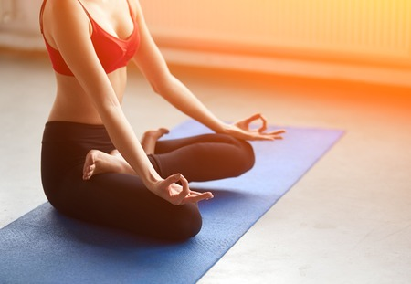 lotus effect: Focus on hand. Close-up of feminine arm during meditation on blue yoga mat with sunlight effect. Unrecognizable young woman sitting in lotus position. Stock Photo
