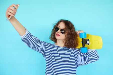 turqoise: Pretty cool young woman in sunglasses with bright yellow skateboard taking picture self portrait on smartphone over vibrant blue turqoise background