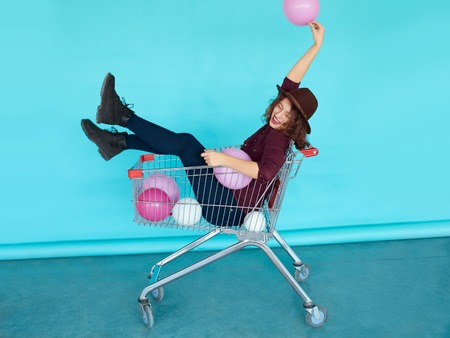 rowdy: Young funky woman sitting in shopping cart over blue color wall. Naughty girl having fun. Indoors, lifestyle