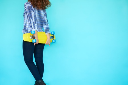 Back view of young funky woman skater dressed in trendy clothes and jeans with her yellow skateboard with copy space on color turquoise background
