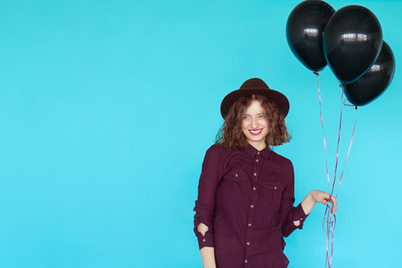 Trendy young happy woman with black balloons having a birthday party. Fashion hipster girl wearing stylish clothes on blue colorful background and copy space