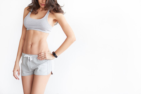 Woman's body in sport wear on white with copy space. Sporty girl with slim figure isolated. Perfect abdomen