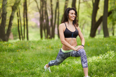 touching toes: woman exercising in park while listening to music. Brunette girl doing her stretches outdoor. Athletic woman stretching after a good workout session.