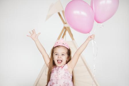 カラフルな風船とドレスの誕生の日に笑みを浮かべて小さな女の赤ちゃんの肖像画。彼女の誕生日を祝って興奮して子供