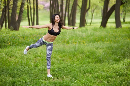 Young girl practicing yoga in nature in the woods on a background of green trees and grass. She balances on one leg. Stock Photo