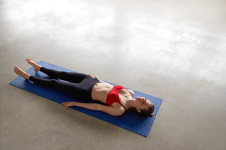 Beautiful young woman working out indoors on blue mat. Girl lying in Shavasana, resting after practice, meditating. Top view