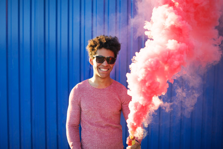 African American young man holding a smoke grenade. Colorful portrait of teenager hipster with red smoke on blue background. Stylish fashion concept with black person