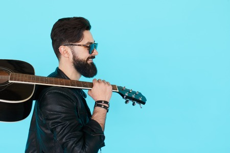 rockstar: Profile portrait of handsome young male musician posing in studio with guitar. Side view of bearded rockstar man holding a guitar over blue background with copy space