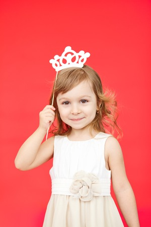 fake smile: young girl as little princess carnival costume, white skirt and crown. Vertical portrait isolated on red background