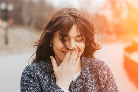 flare up: Happy laughing beautiful large woman. Close up plus size girl smiling on a cold autumn day with lens flare effect Stock Photo