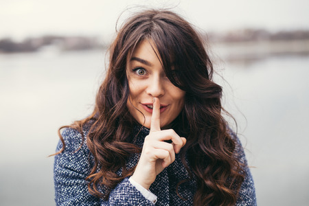 shushing: cute woman with long black hair holding her finger on her mouth as she was keeping a secret