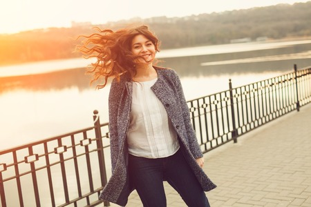 mulher com excesso de peso feliz andando na rua da cidade à beira do lago. Retrato dinâmico da menina com vento no cabelo ao pôr do sol, com efeito o alargamento do sol