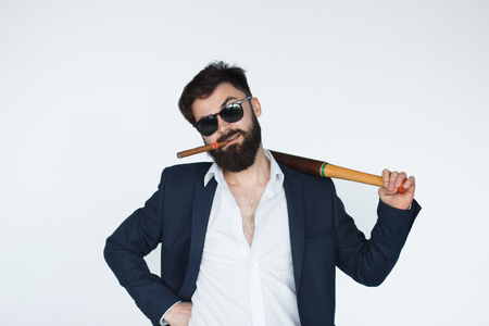 provoked: angry young man wearing black suit and sunglasses holding a baseball bat isolated on white background. Conflict and problems concept