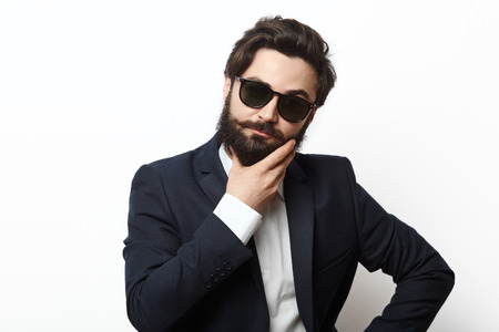 dudando: serious man in black suit thinking and hesitating, isolated on white. Bearded male wearing sunglasses