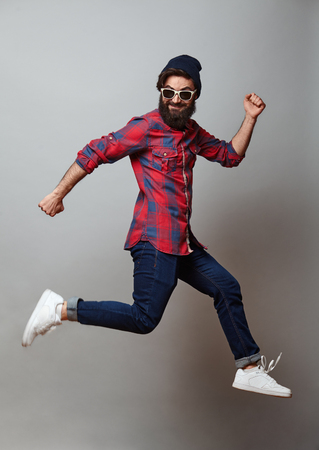 happy excited jumping young bearded man. Funny portrait on young casual male model in humorous jump on grey background. Archivio Fotografico