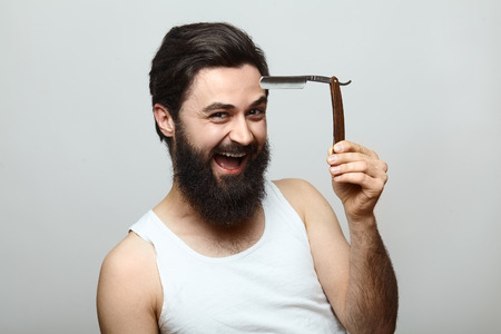 good grooming: Sexy handsome happy young man with a shaving razor smiling over grey background. Morning routine Stock Photo
