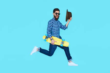Pretty young bearded man jumping with yellow skateboard against the colorful wall. Hipster in motion on blue background