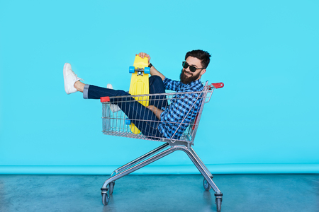 Carefree hipster fun. Side view of cheerful young man sitting in shopping cart with bright skateboard over colorful wall Stok Fotoğraf