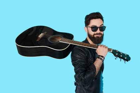 Rock musician posing with guitar on blue color background. Stylish bearded man in sunglasses and leather jacket holding a black guitar Archivio Fotografico