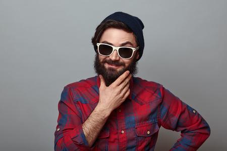dudando: hombre de la barba reflexivo sonriendo y vacilantes. sobre fondo gris Foto de archivo