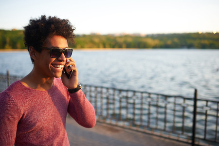 somebody: Happy afro american young man talking on phone. Cheerful student calling somebody on sunset with copy space Stock Photo