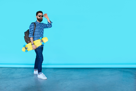 Full body portrait of young fashionable hipster man posing over blue background with copy space. Bearded male holding yellow skateboard and smiling Stok Fotoğraf