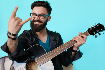 Happy young punk rocker with a guitar and dark sunglasses on blue background. Man in leather jacket showing Rock sign