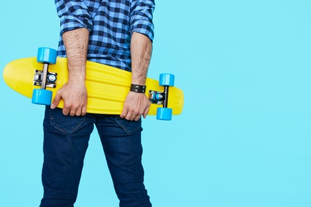 tenager: Close up of Hipster holding his yellow penny skateboard with copy space. Cool, Tenager back view