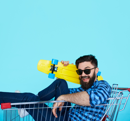 Carefree hipster fun. Side view of cheerful young man sitting in shopping cart with skateboard over blue wall