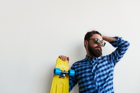 subculture: close up of bearded hipster in checkered shirt holding yellow skateboard isolated over white background with copy space