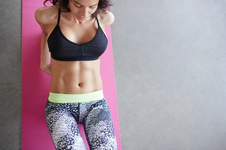 laying abs exercise: Top view of young woman lying on yoga mat in gym. Above portrait of fitness woman close up abs on floor with copy space