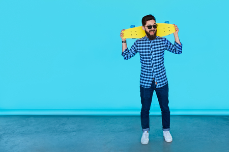 Full body of Casual handsome attractive man hipster guy holding a yellow skateboard over blue background with copy space. Stock Photo