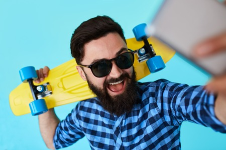 young handsome bearded hipster man makes a selfie on a blue background while holding a skateboard. Stylish male making a self portrait with smartphone