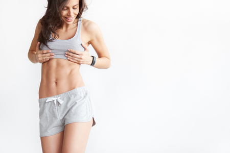 Slim tanned womans body over white background. Perfect six pack abs with copy space