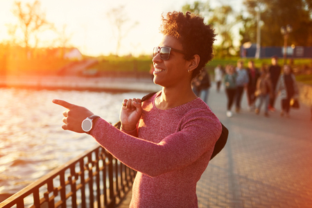 Freundliche junge trendigen afrikanischen schwarzen Mann zu Fuß rund um die städtischen Stadt, die Spaß haben
