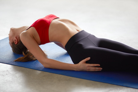 strengthening: Close up side view of young woman doing gymnastics in fitness studio or yoga warming up exercises for spine, backbend, strengthening back muscles