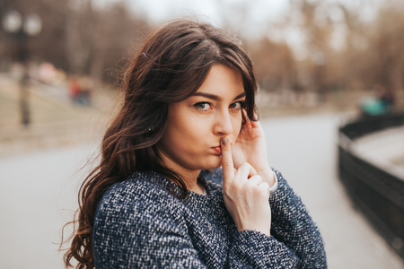 Closeup portrait secretive young woman placing finger on lips asking shh, quiet, silence looking. Human face expressions, sign emotion