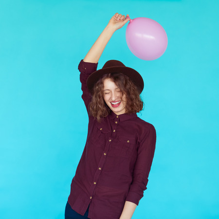 artsy: Casual lifestyle with beautiful hipster girl holding a pink balloon and smiling against blue background, isolated.