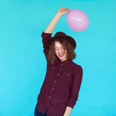 estereotipo: estilo de vida casual con la muchacha hermosa inconformista que sostiene un globo de color rosa y sonriente sobre un fondo azul, aislado.
